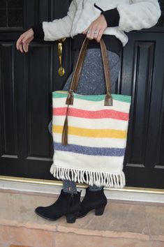 4e38d8942a0a8 These signature totes have handles and a tassel made from rich brown  leather. The bag