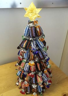 christmas tree made of miniature candy bars, with a six pointed paper star in gold, placed on wooden desk with light background christmas candy ▷ 1001 + Ideas for DIY Christmas Gifts and Festive Decoration Christmas Fayre Ideas, Christmas Craft Fair, Christmas Activities, Kids Christmas, Christmas Crafts, Christmas Decorations, Christmas Sweet Cones, Cone Christmas Trees, Sweet Trees