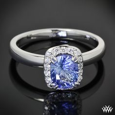 """Set in 18k White Gold, this """"Guinevere"""" Solitaire Engagement Ring has been customized to hold a 1.20ct Cushion Cut Blue Sapphire. The squared 4 prong halo holds 0.12ctw A CUT ABOVE® Hearts and Arrows Diamond Melee."""
