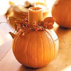 Fall themed weddings: floral pumpkin centerpiece with nutmeg scented candles