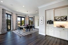 A striped rug corrals the furniture at one end of this open concept space and turns it into a chic dining room. Black-and-white patterned curtains are the perfect lively counterpart.