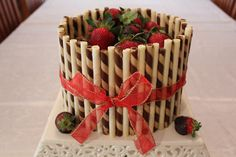 Chocolate cake covered in chocolate ganache, surrounded by wafer sticks, topped with strawberries.