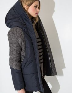 """Stay dry and cute this winter with our Aya Puffy Hood Coat. It is a navy puff coat with grey tweed detailing. Features two front zipped pockets, adjustable hood, full feather padded lining, and zipper button closure down front. Throw this super cool feather padded puff coat over a turtleneck sweater, mom's jeans and combat boots for a hip street look. *27""""/68cm length*Model is wearing size small and model's height is 5'10""""/178cm.*Made in Korea."""