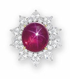 A STAR RUBY AND DIAMOND RING  Centering upon a star ruby weighing 9.05 carats, to the brilliant and pear-shaped diamond radiating surround, mounted in platinum and 18k yellow gold.