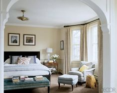 Lively patterns on the armchair and bed pillows add a dose of energy to the room's subdued neutral palette.