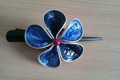 """Nespresso Schmuck - Haarspange """"Blaue Lagune""""  Bildschöne schwarze Haarspange mit handgefertigter blauer Blume als Verzierung. Die Blume besteht aus fünf blauen Alluminiumblüten und einer roten Zierperle. Ein toller Hingucker für jede Gelegenheit.  Jedes Produkt wird handgefertigt und ist ein Unikat. Das Produkt kann daher etwas von der Abbildung abweichen.  Die Haarspange ist auf Nachfrage auch in vielen anderen Farben (blau, grün, schwarz etc.) erhältlich."""