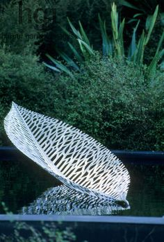 New Zealand garden. Silver-Gilt flora. Metal leaf sculpture by Virginia King floating on water. Xanthe White RHS Chelsea Show 2006. Contemporary Ornaments Ponds Jerry Harpur Please read our licence terms. All digital images must be destroyed unless otherwise agreed in writing. Photograph by: www.harpurgardenlibrary.com Contact: Harpur Garden Library 44 Roxwell Road Chelmsford Essex CM1 2NB, UK