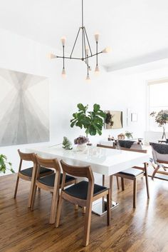 Clean, and modern dining room with large art, a triad chandelier, and wooden chairs