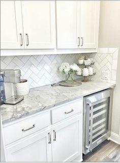 Quartz counters with Daltile M313 marble 3x6 herringbone tile backsplash.