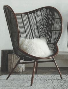 The Roost Olaf Chair with its sinuous rounded lines inspired by Danish Modern design invites lingering in the generous seat and enveloping arms. Stained rattan in mahogany and ebony tones is artfully hand-woven to create this graceful chair.