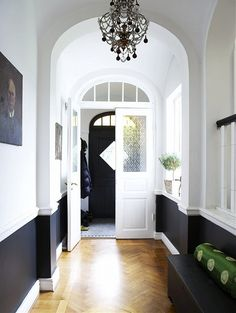 grey marble tile with black/white border into wood hallway