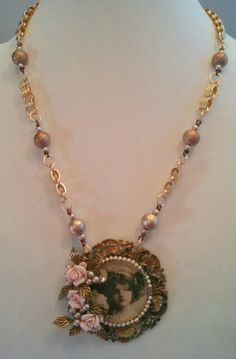 Beautiful vintage look focal with floral, leaf, and pearl accents.  Necklace made of satin matte gold book chain, large Spectra beads and Swarovski pearls.  Designed by Marcia Tuzzolino of Aurora Designs on fb.