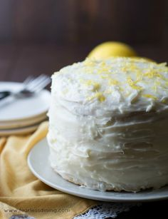 A Gluten Free Lemon Layer Cake is sitting on a cake plate.