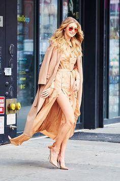 Gigi Hadid wears a tan military maxi dress with a tan coat, aviator sunglasses and nude pumps.