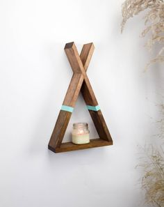 Dimensions: Interior: Base: 9.5 inches Height: 11 inches Depth: 3.5 inches Exterior: Base: 11 inches Height: 19 inches Depth: 3.5 inches Weight: 4 lbs This listing is for one Teepee shaped floating shelf with aqua stripe accent. Hanging this shelf is a breeze! We include a 2 inch finishing nail to slide the teepee shelf on at its highest point. It can also rest on any flat surface. This teepee shelf is a unique addition to your decor, perfect for displaying your favorite items, succulen...
