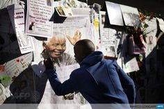 SOUTH AFRICA, Pretoria: A man leaves a note on a wall where well wishers left messages for former South African President Nelson Mandela outside the MediClinic Heart Hospital in Pretoria July 2, 2013. Mandela, who turns 95 next month, was rushed to hospital more than three weeks ago with a recurrent lung disease. AFP PHOTO/MARCO LONGARI