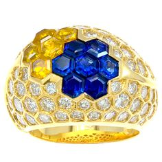 A chic Diamond, Blue & Yellow SapphireFrench Dome ring set in 18 karat Gold. This ring is embedded with approximately 3.60 carats of high quality round diamonds. This ring centers octagonal cut Blue & Yellow Sapphires which displays a geometric floral design. This jewel weighs 14.1 grams and has French marks.Circa 1980s