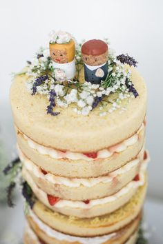 Naked wedding cake with wine cork bride and groom cake toppers.