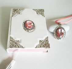 of white leather art journal with pink glass cristal pearl in front, and a pink pendant necklace. Unique art gift for women and girls. Leather Notebook, Leather Journal, Notebook Art, Pink Pendants, Necklace Set, Pendant Necklace, Pearl Pendant, Handmade Art, Decoration