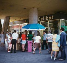 "People at a souvenir-vendor infront of a ""delikat""-store at Friedrichstraße / Unter den Linden in Berlin-Mitte (30.07.1973)"