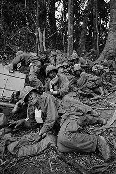 22 Nov 1967, Near Dak To, South Vietnam --- Dak To, South Vietnam: Members of the 173rd Airborne Brigade, many wounded during the bitter siege of Hill 875, huddle together here, wary of sniper fire, as they wait for evacuation helicopters. Reinforced American troops seized most of the strategic Hill 875 and dug in within hand grenade range of North Vietnamese fortress at the top. Fighting in the Central Highlands has been the fiercest in the Vietnam conflict.