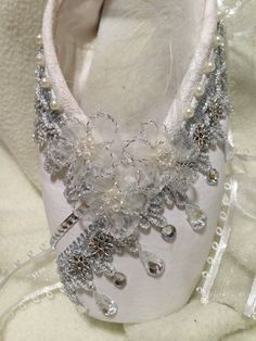 This is a Pointe Shoe decorated with inspiration from Swan Lake, one of the most popular Ballet dances. It is painted with white acrylic paint and embellished with sequins, pearl beads, rhinestones, feathers, and silver flowers as a stunning accent.  It is one of a kind and not meant to be worn! It is meant to be used as decoration, or a keepsake as a reminder of this lovely ballet dance.  *please note that this is a well loved pointe shoe that was once used in actual performances. There…