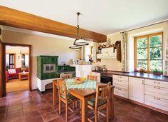 Propojením bývalého vejminku a malé kuchyňky vznikla obývací kuchyně s kachlovým sporákem a lákavým zápecím.