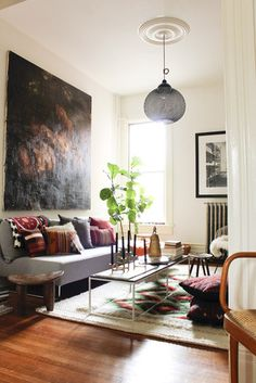 oh wow - I love everything about this!  The dramatic art, the lighting fixture, kilim throw pillows, taper candles and tall plant, wood floors, lush rug, white walls, ceiling medallion...!!!!!
