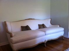 """Vintage Sofa - A modern take on Louis style  Kiln dry wood, hand-carved frame with white herringbone upholstery and antique brass nailheads. The sofa is comfortable, solid and comes with an extra set of white cushion covers. High quality from a major designer. Dimensions: 76""""w x 36""""d x 32""""h (overall) 19.5""""h (seat height); 21.25""""h (arm height)"""
