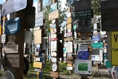 """Signpost Forest, Watson Lake, Yukon.  I spy a grizzly bear, a polar bear, the word """"TUNNEL"""",  two tin plates, and """"JIM AND KATHY.""""  06/2013."""