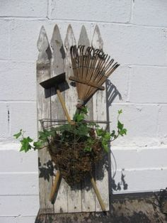 The Enterprising Family:  Frugal Decorating...The gardener's 'Coat of Arms.'  Old fence panel portion or pickets, a couple of garden tools - criss crossed and a moss filled wire wall basket w/some ivy!  I LIKE it!