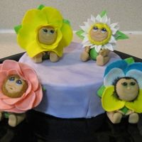 vanilla cake, vanilla frosting with purple marble fondant and figures are fondant flower babies (ann geddes style) each baby took about two hours