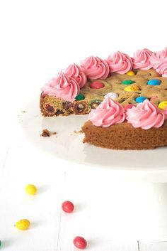 Need a dessert recipe idea for Easter that looks and tastes delicious? This gorgeously golden cookie cake is loaded with chocolate candy easter eggs and topped with pink buttercream frosting.