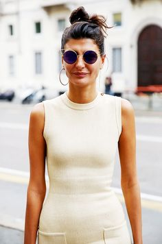 Giovanna Battaglia wears a single gold hoop earrings with a body-con dress and round sunglasses