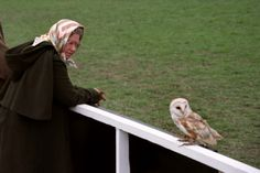Britain's Queen Elizabeth II keeps a close eye on a Barn Owl which landed close to her as she…