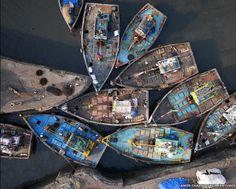 O fotógrafo Amos Chapple usou uma câmera presa a uma aeronave não-tripulada (drone) para capturar belas imagens aéreas na Índia. Nesta foto, barcos de pesca na entrada das docas Sassoon, em Mumbai (Foto: Amos Chapple/ Rex Features)