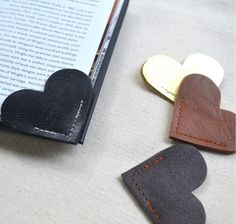 "You're sure to be sweet on this heart-shaped bookmark! Made of two pieces of natural leather, this bookmark slips over the corner of your page to keep your place. Each heart measures roughly 2""x2"" and due to the nature of natural materials and handmade items, you may notice some variations. Handmade from 100% natural leather in the United States by Jennifer Lesley Design. Available in glossy black, medium brown, and gold. Includes ONE bookmark."
