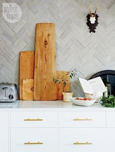 Style at Home - kitchens - antler mount, modern white cabinets, brass cabinet pulls, concrete herringbone backsplash