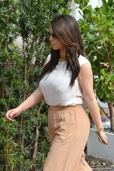 Kim Kardashian steps out in a white blouse and tan wide-legged trousers in Miami