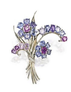 WHITE GOLD, MULTI-COLORED SAPPHIRE/DIAMOND 'REFLECTION' BROOCH, TRABERT & HOEFFER MAUBOUSSIN, CIRCA 1940. Designed as a floral bouquet set with numerous blue, pink and purple sapphires weighing approximately 25.00 carats, further accented by single-cut diamonds, signed Trabert & Hoeffer Mauboussin, stamped Reflection.