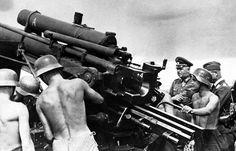 Operation Barbarossa: A German officer watches as an artillery team shells a city.