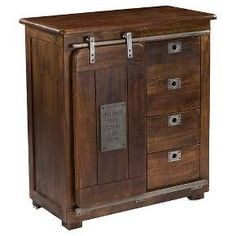 This cabinet has an interesting and unique design. The Warm Brown Mango finish is neutral toned and rich. A sliding barn style door reveals an open space with two shelves on the left or a stack of four drawers on the right. Metal hardware accents the drawers, and the door has a unique metal plaque to continue the antique theme.