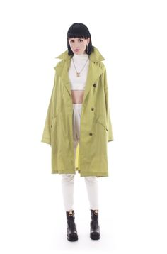 Iridescent green Mycra Pac raincoat. 🔹 Unique pea green nylon / poly blend with a lovely sheen. 🔹 Medium to light weight, high quality material. 🔹 Wide oversized silhouette looks great on all sizes. 🔹 Rounded bronze tone textured button asymmetrical closures. 🔹 Tab with button closure beneath neckline at collar. 🔹 Angled flap pockets with button closure. 🔹 Dropped shoulder seams. 🔹 Wide winged notched collar. 🔹 Unlined. 🔹 Water resistant material great for days with light rain...