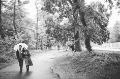 Couple walk along a path with an umbrella during their rainy engagement session in Prospect Park with NYC wedding photographer Ben Lau.