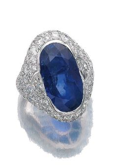SAPPHIRE AND DIAMOND RING, BULGARI, 1960S. Set to the centre with an oval sapphire, the mount set with demi-lune and brilliant-cut diamonds, size 531/2, signed Bulgari.