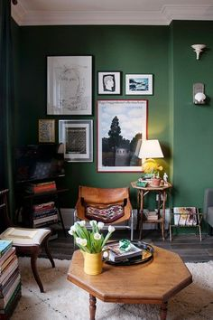 Dark Green Living Room in Green Paint Ideas on HOUSE. Forest green sitting room with gallery wall, retro wooden furniture, plenty of books and fresh tulips.