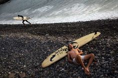 Omar Diaz takes a nap after surfing in the Pacific Ocean on the coast of Lima, Peru, on March