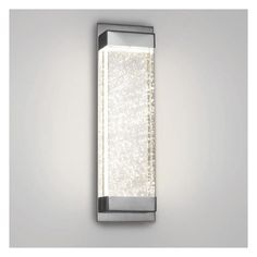 A simple modern design that features a solid crystal block illuminated from within the frame that creates magnificent sparkles as the bubbles within catch the light. Polished nickel fittings and concealed hardware complete this curiosity inspiring sconce.