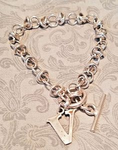 """Very unique and intricate sterling silver chain link bracelet with a toggle clasp and """"V"""" pendant/charm on it. Heart Jewelry, Jewelry Rings, Silver Jewelry, Jewelry Watches, Modern Jewelry, Fine Jewelry, Sterling Silver Chains, Jewelry Stores, Pendant"""
