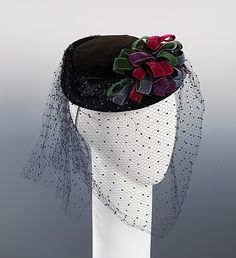 """Madame Suzy, 1939.  Excerpt from @metmuseum website """"A hat like this, from a prominent Parisian designer of the 1930s, would have been a prized commodity for American women. The skillfully applied jewel-tone ribbons and the refined quality of the veiling are indicative of the materials and techniques used in French millinery ateliers. However, the late 1930s marked a turning point, war interrupted fashion production in Paris and allowed for American designers to gain recognition in the…"""